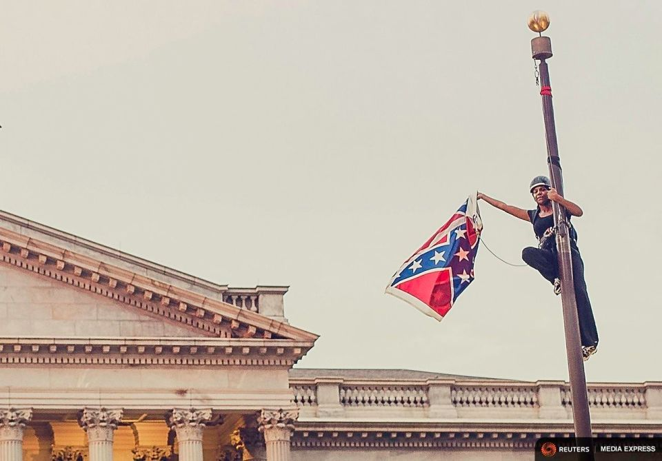 Bree Newsome taking down the Confederate flag. Image credit unknown.
