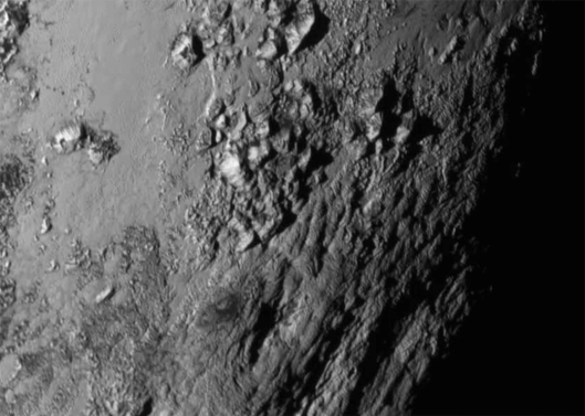 The surface of Pluto, revealing mountains about the same size and age of the Rockies.